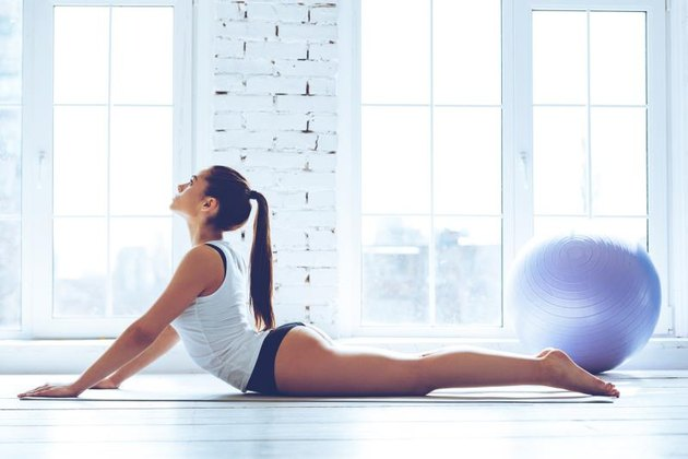 Side view of young beautiful young woman in sportswear doing cobra pose while lying on the floor in front of window at gym