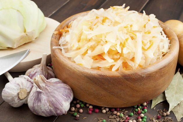 Sauerkraut with carrot in wooden bowl, garlic, spices and cabbage