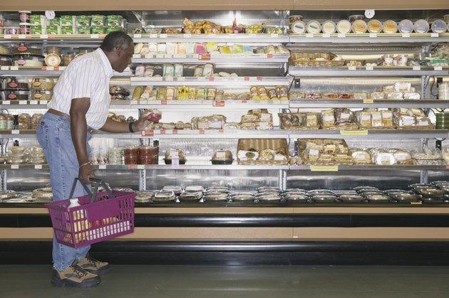 Elderly man shopping at a supermarket holding a shopping basket