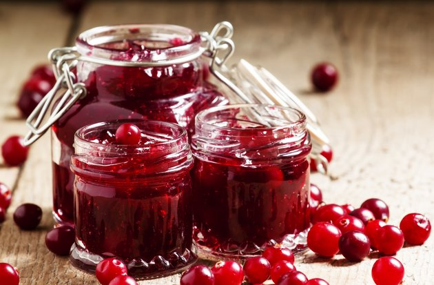 Delicious cranberry jam in glass jars and fresh cranberry