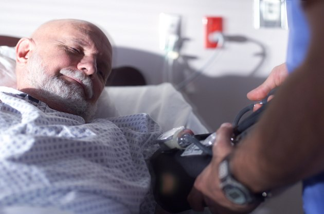 an elderly caucasian man lies in a hospital bed as a nurse checks his blood pressure