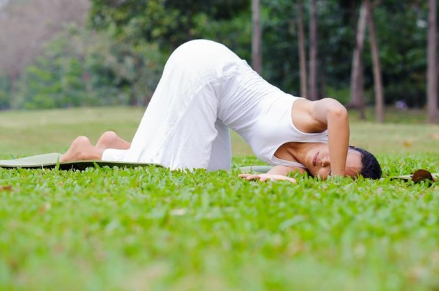 Beautiful woman practicing yoga in the park.Thread The Needle.