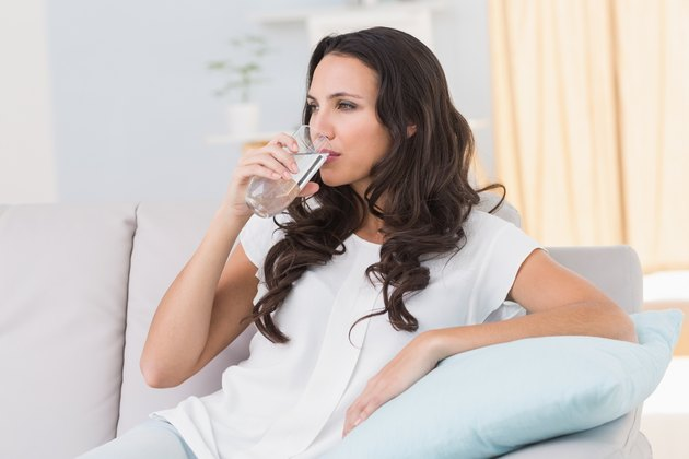 Pretty brunette drinking water on couch