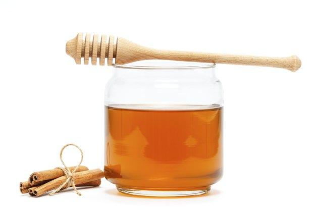 Honey in jar with dipper and cinnamon on isolated background