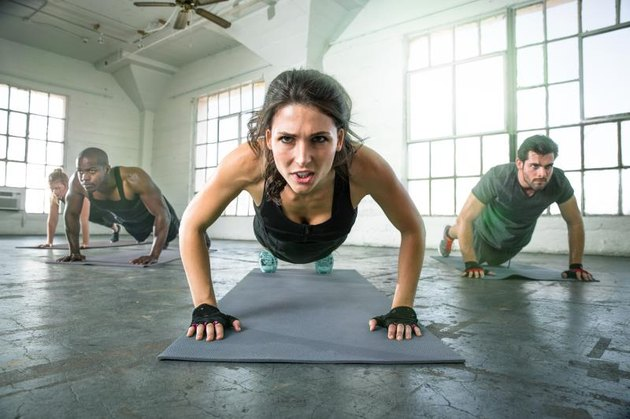 Female leads cross fit power yoga group class strength determination drive as physical trainer instructor in push ups intense focused expression. Fitness exercise gym group muscle building workout with woman leading group of people