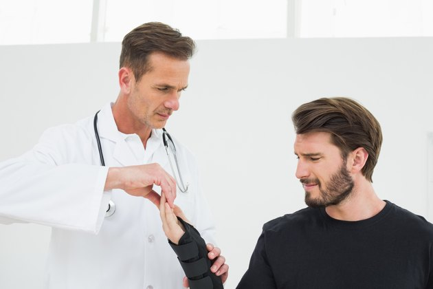 Male physiotherapist examining a young man's wrist in