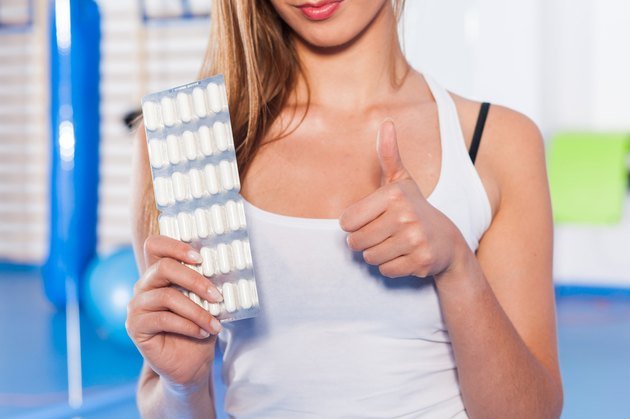 Portrait of a young woman holding weight and vitamins (pills).