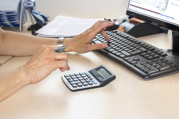 Businesswoman typing on calculator