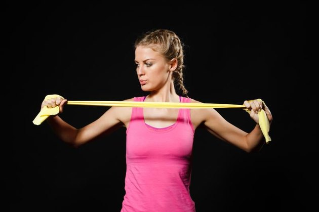 Beautiful young woman is exercising with rubber band.