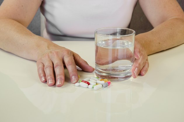 hand with pill and glass of water