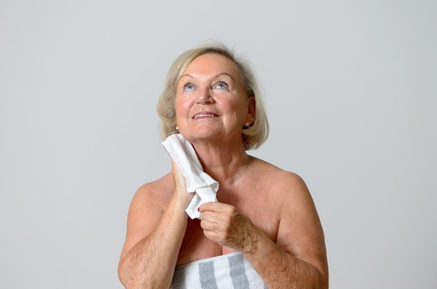 Happy Middle Age Woman Drying her Neck with Towel