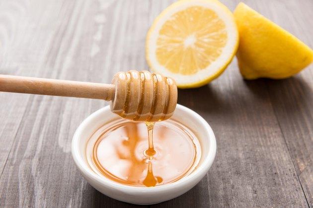Bowl of sweet honey and lemons on wooden table