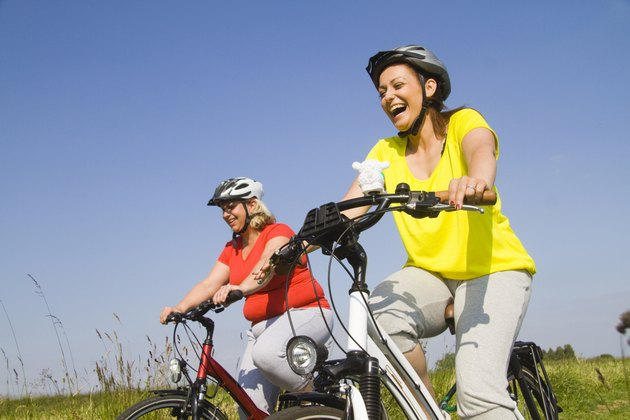 Two friends riding bicycles through field