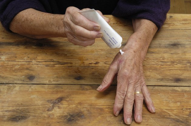 Elderly woman putting on ointment