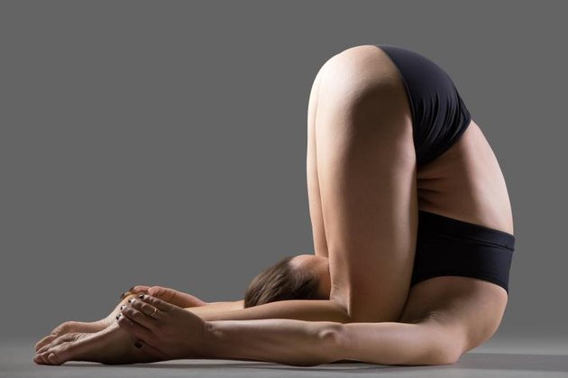 Beautiful young fit woman in sportswear shorts doing sport exercises, shoulder stand, karna pidasana, Knee to Ear or Deaf Man Posture (variation of Raja Halasana), studio image on gray background