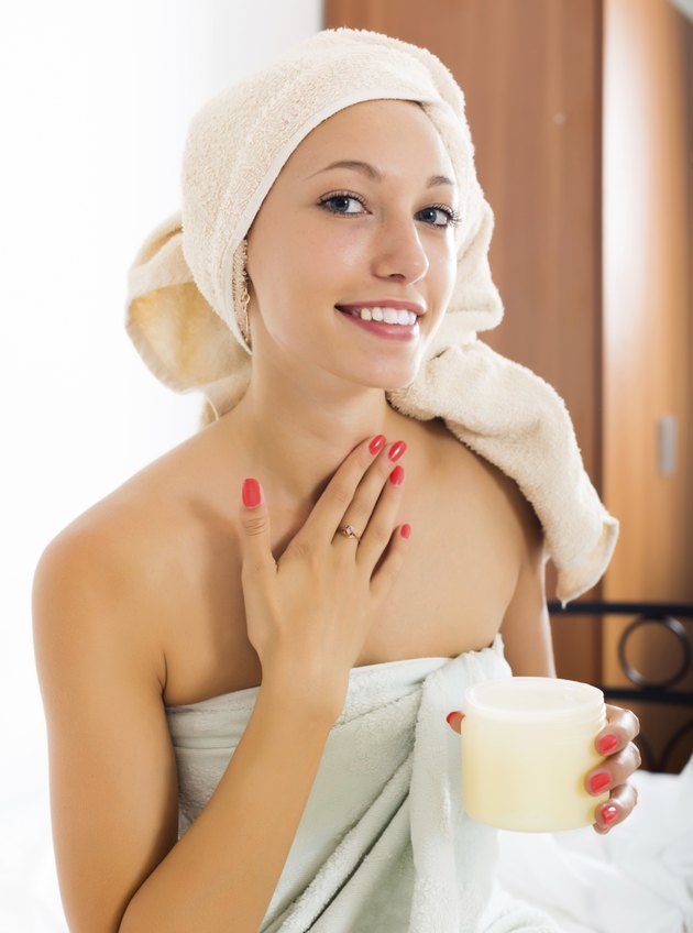 young woman putting cream on face