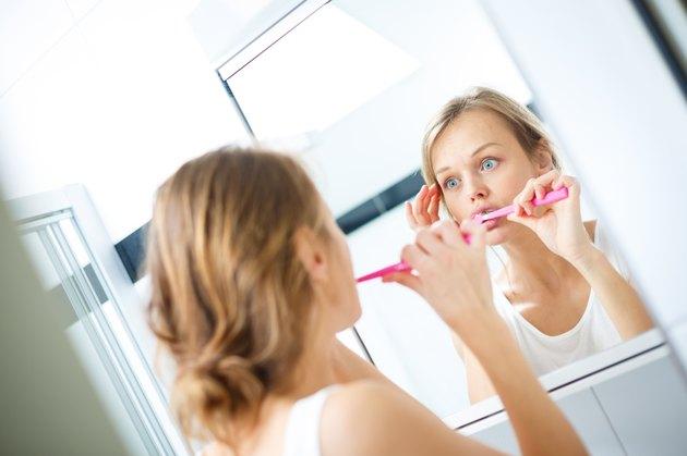 Pretty female brushing her teeth
