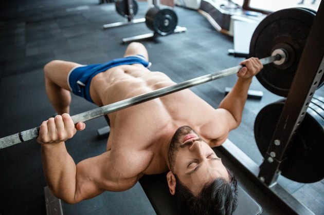 Muscular man doing bench press