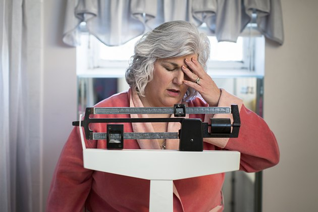 Unhappy mature woman on bathroom weighing scales