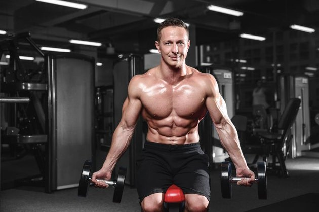 Fitness strength training workout bodybuilding concept background - muscular bodybuilder handsome man doing exercises in gym naked torso