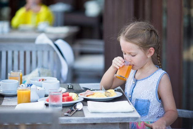 Adorable girl drinking apple juice for breakfast in outdoor cafe