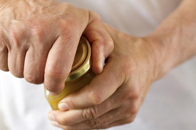 Strong Male Hands Twisting a Stubborn Jar Lid (Close-Up)