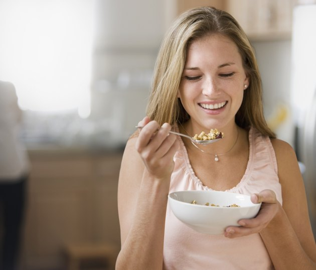 Beautiful young woman holding bowl with cereal smiling