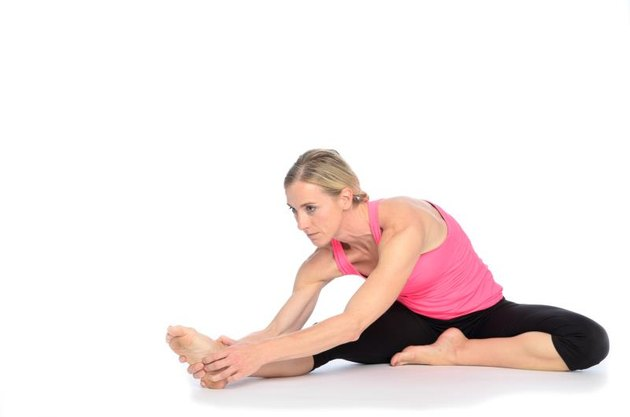 Single gorgeous woman in pink and black outfit doing hamstring stretch over white background with set down shadow