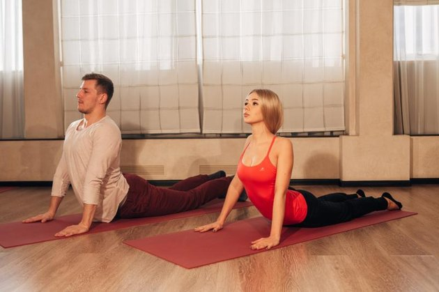 young woman and man doing yoga exercise Cobra in special studio