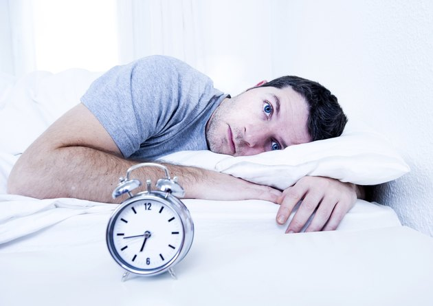 man in bed suffering insomnia and sleeping disorder