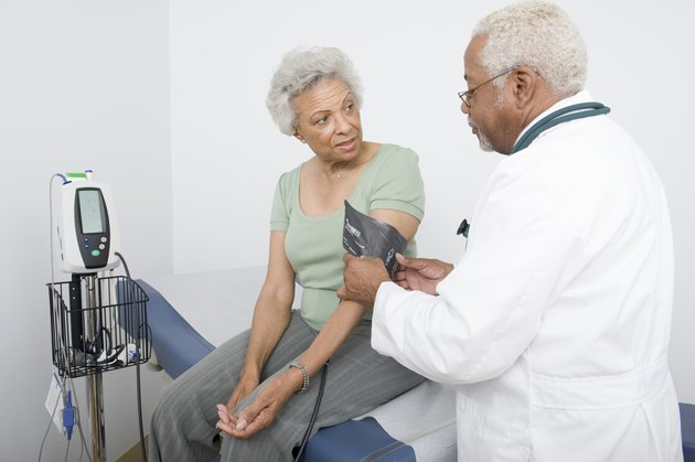 Doctor Measuring Patients Blood Pressure In Clinic