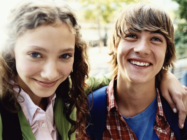 Teenage Girl Stands Smiling With Her Arm Around Her Friend