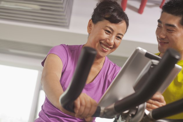 Woman smiling and exercising on the exercise bike with her trainer