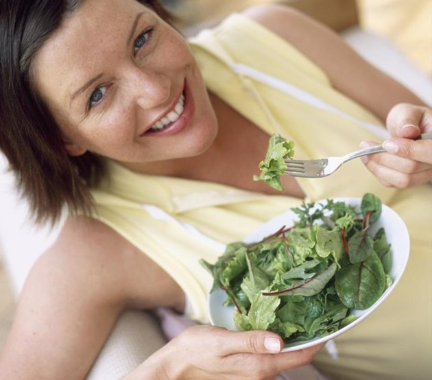 Healthy eating. Woman eating salad leaves. Fruit and vegetables are rich in minerals and vitamins, as well as being low in fat. Green vegetables are particularly rich in iron, an essential mineral in the body.