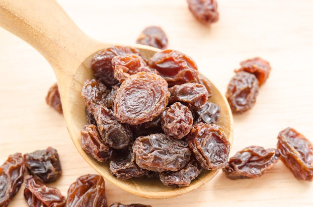Raisin in wooden spoon.