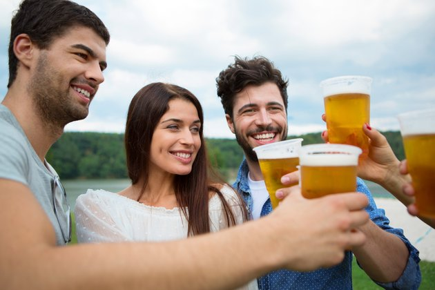 Group of friends toasting with beer in plastic glasses