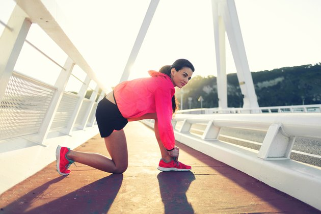 Portrait of a young female jogger dressed in sportswear tie shoelaces while taking break between evening run outside,