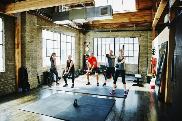 Athletes doing kettle bell swings during class