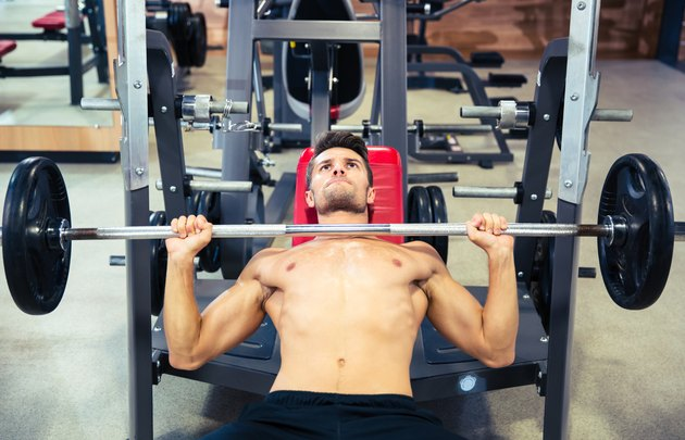 Man doing exercises with barbell to burn fat