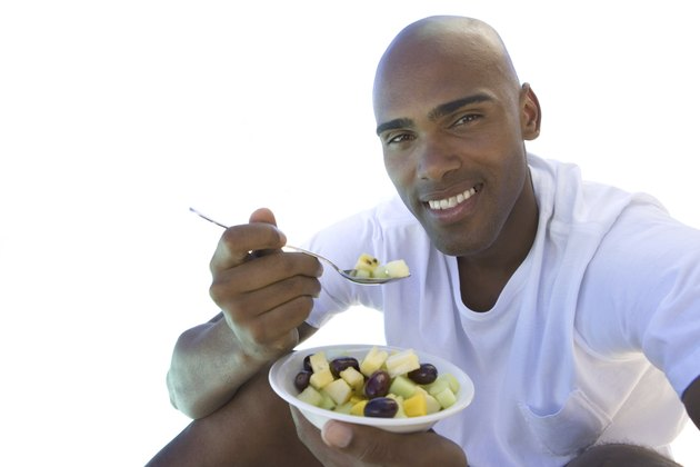 man sitting down eating bowl of fruit, cut out