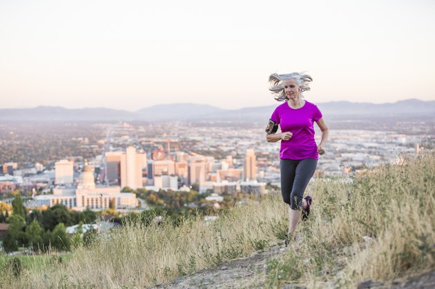 Caucasian woman running on hilltop over Salt Lake City, Utah, United States