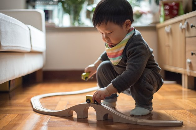 Crouching toddler boy playing toy train