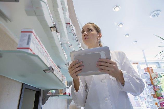 Pharmacist in pharmacy holding digital tablet