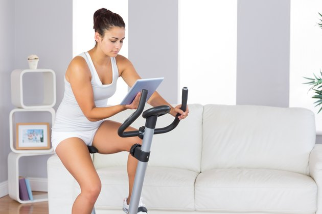 Concentrated slender woman training on an exercise bike while using her tablet