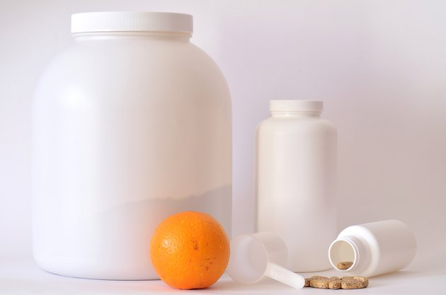 Big jar of protein powder, bottle of pills, orange