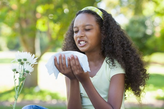 Young girl sitting by flower and sneezing in the park