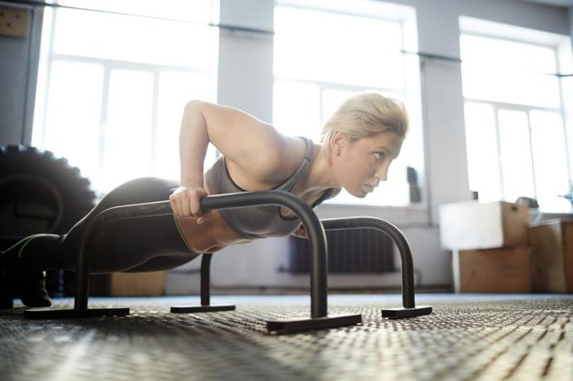 Girl sweating while doing planks or push-ups in gym