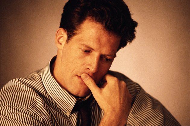 Businessman looking down with finger on lips