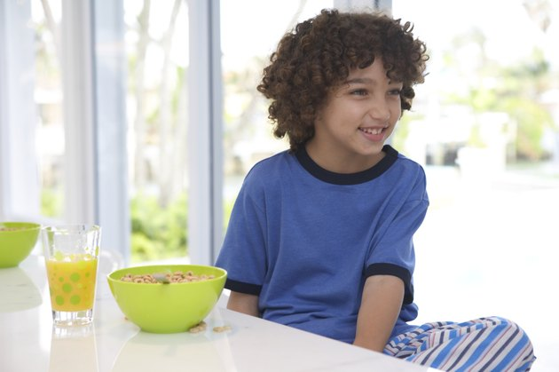 Boy (8-10) at breakfast table, smiling