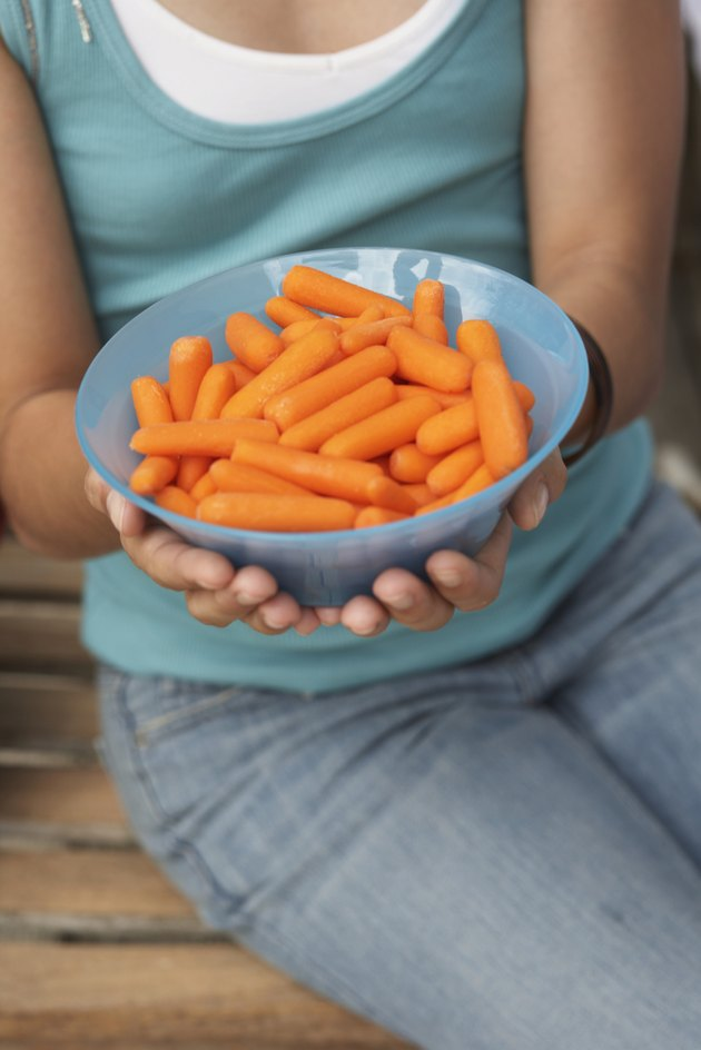 Girl (13-15) holding bowl of peeled baby carrots, close-up